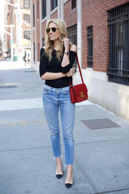 Модель в обрезанных джинсах, черная футболка с открытыми плечами. красная сумочка