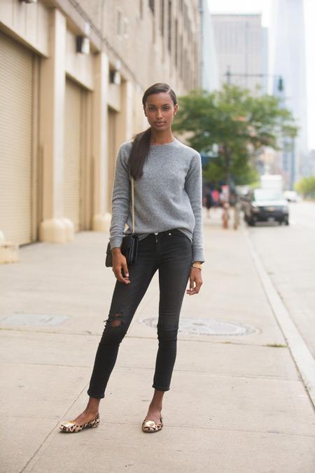 Модель в рванных джинсах и серой кофточке с рукавом