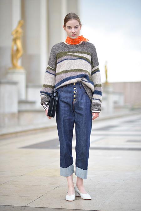 Модель в синих джинсах и полосатом свитере, белые туфельки