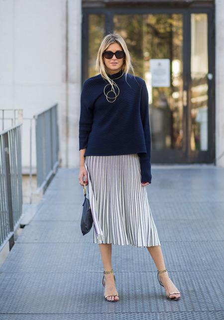 Модель в светлой плисированной юбке и темно синем свиншоте