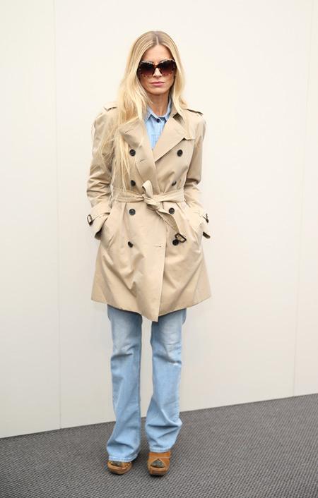 Модель в светлых джинсах и бежевом плаще на поясе