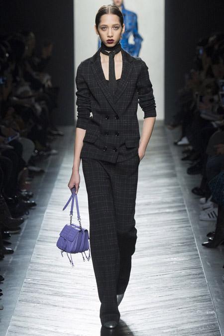 Модель в темно-сером костюме в клетку