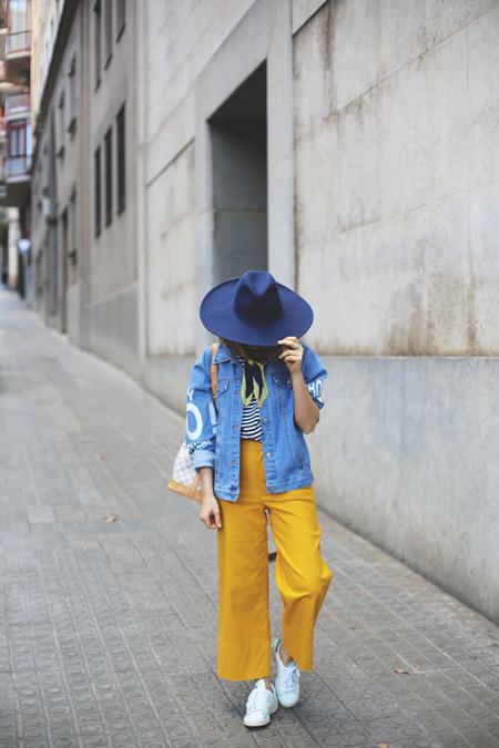 Модель в желтых брюках, тельняшке, джинсовая куртка и синяя шляпа