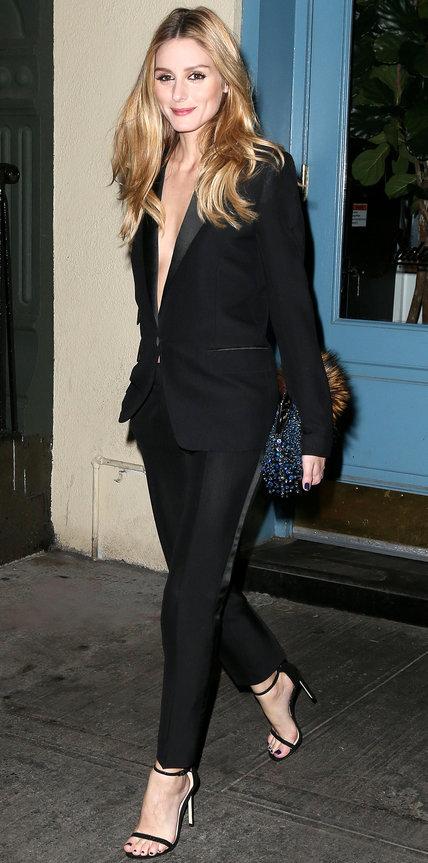 Оливия Палермо в черном брючном костюме с глубоким декольте и босоножках
