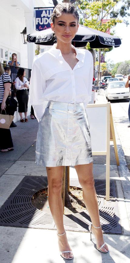 Зендая в блестящей мини юбке и белой рубашке