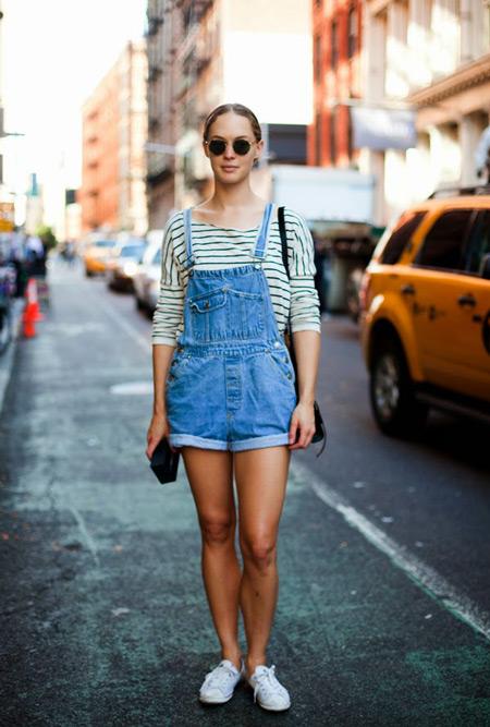 Девушка в джинсовом комбинезоне шортах, тельняшке и белых кедах