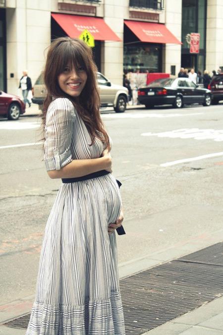 Беременная девушка в белом длинном платье с тонкую полоску