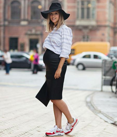 Беременная девушка в черной юбке карандаш, светлая рубашка, кроссовки и черная шляпа