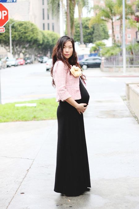 Беременная девушка в длинном черном платье и нежно розовом жакете