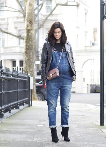 Беременная девушка в джинсовом комбинезоне, ботильоны и кожанная куртка