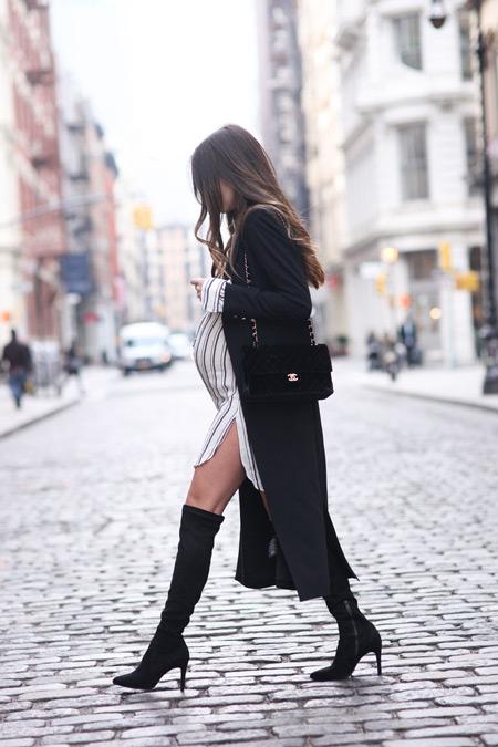 Беременная девушка в платье-рубашке, длинное черное пальто и сапоги-чулки