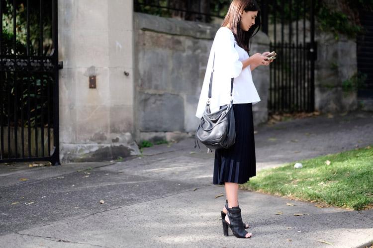Девушка с черной юбке в складке, белаю блуза и ботильоны с открытой пяткой и пальцами