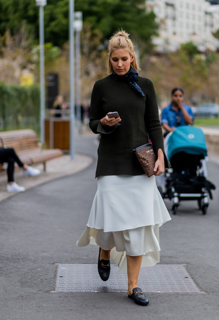 Девушка в белой юбке, темная водолазка и клатч