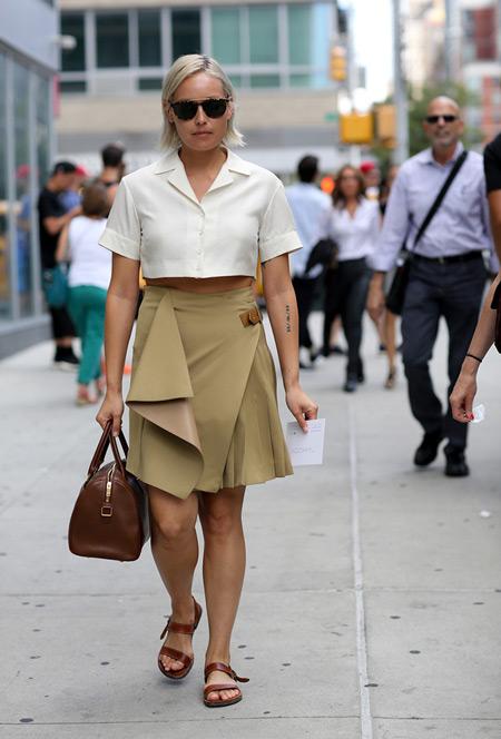 Девушка в бежевой юбке, коричневые сандалии и сумка, белый укороченный топ на пуговицах
