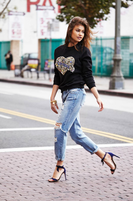 Девушка в черном свитшоте и голубых джинсах