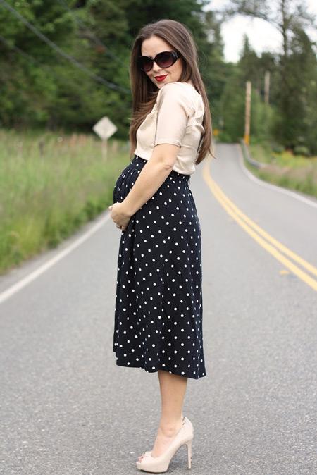 Девушка в черной юбке миди в горох, бежевая блуза и туфли