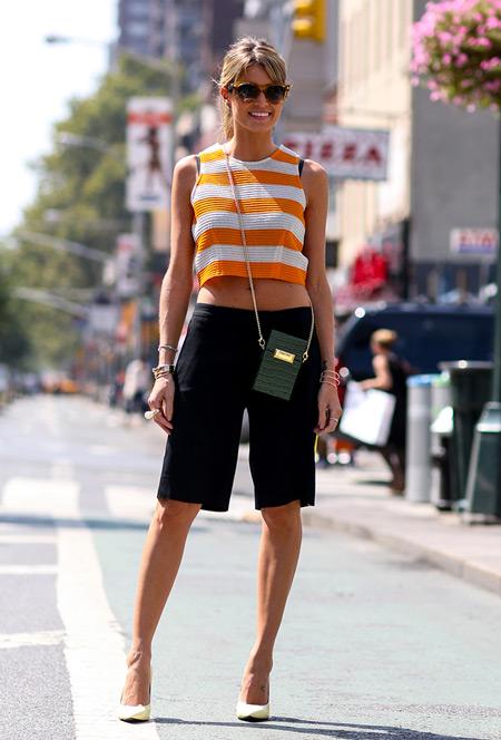 Девушка в черных бермудах, полосатый бело-оранжевый кроп топ