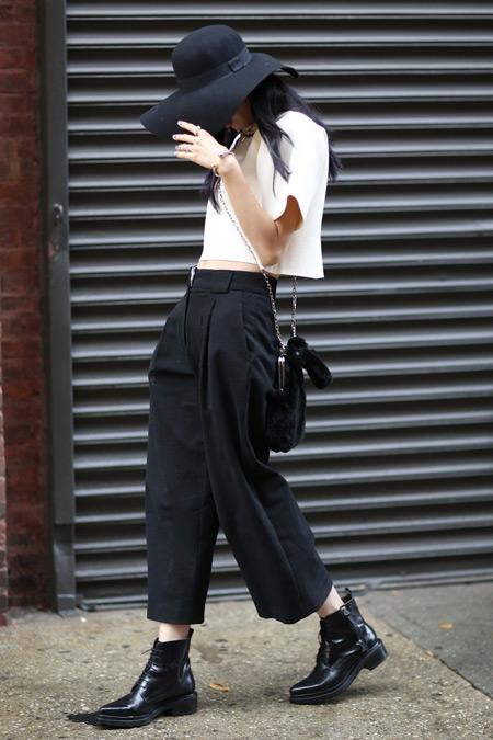 Девушка в черных брюках, шляпе и белый кроп топ