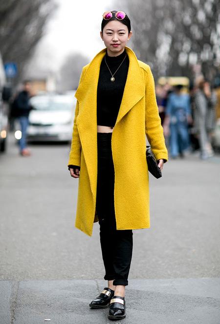 Девушка в черных джинсах, кроп топ и желтое пальто
