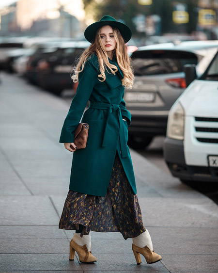 Девушка в длинном изумрудном пальто