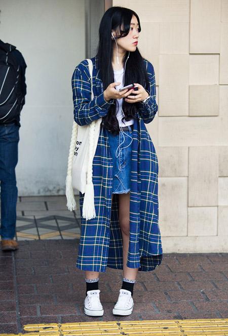 Девушка в джинсовой мини юбке, ббелый топ синий плащ в клетку