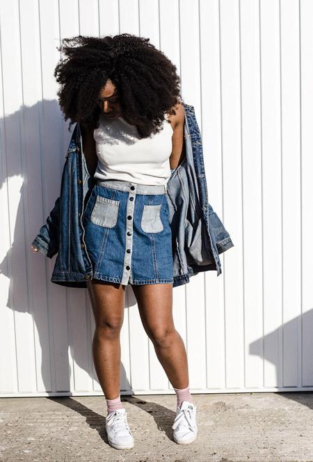 Девушка в джинсовой мини юбке с накладными карманами, белый топ и джинсовая куртка