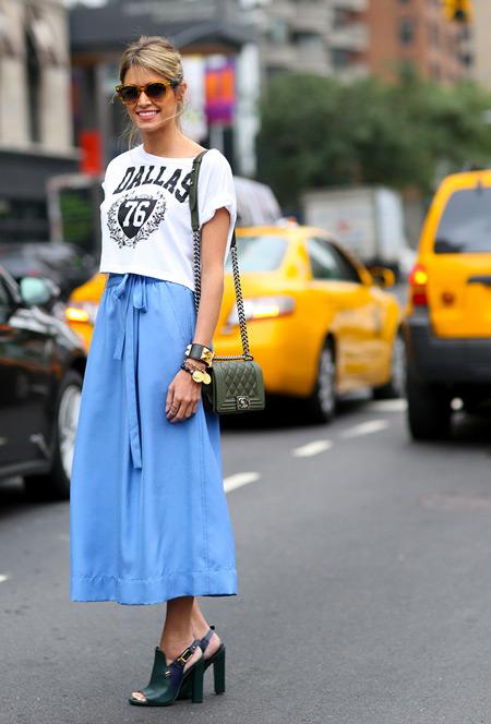 Девушка в голубой юбке, кроп топ с надписями и сумка и босоножки болотного цвета-----------------------------9-------бджэ