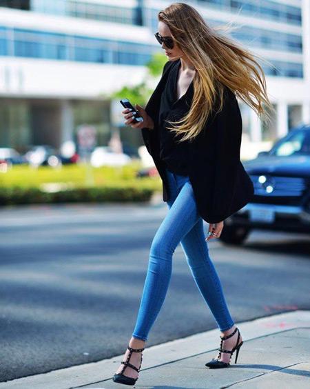 Девушка в голубых джеггинсах и черной блузке