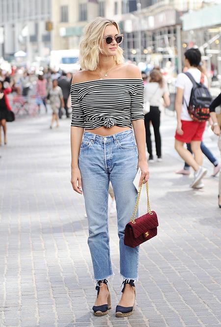 Девушка в голубых джинсах, полосатый кроп топ и бордовая сумочка