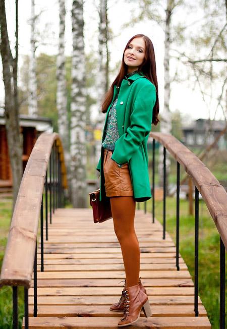 Девушка в изумрудном пальто и рыжих шортах