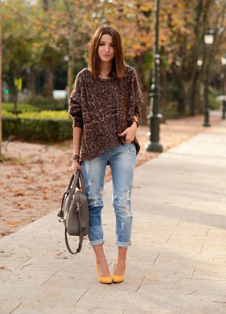 Девушка в коричневом свитере и голубых джинсах