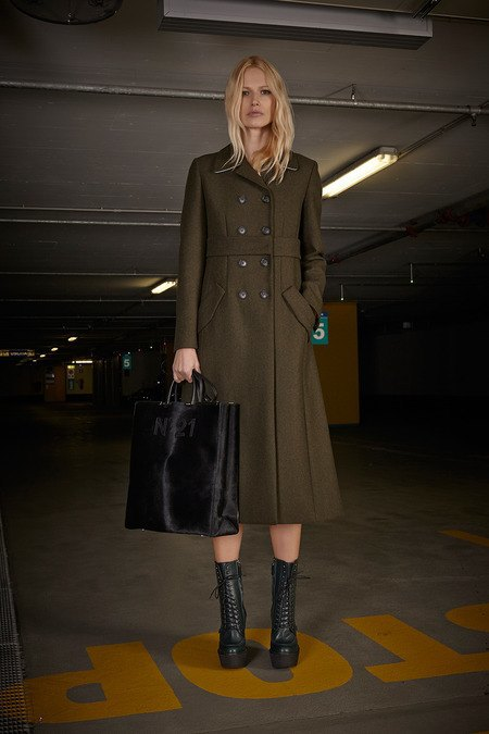 Девушка в пальто цвета хаки и ботинках на шнуровке