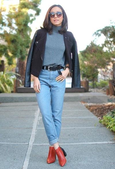 Девушка в сером свитере и голубых джинсах