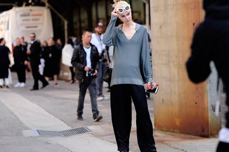 Девушка в широких черных штанах и фуктболке свободного покроя