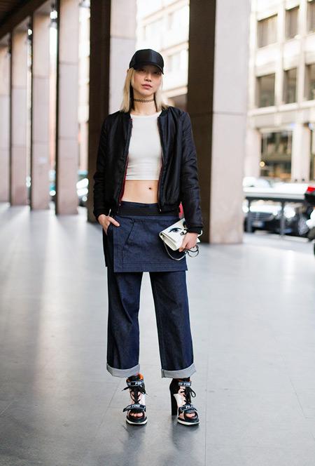 Девушка в широких джинсах, белый кроп топ и кожанная куртка