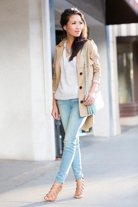 Девушка в свтелом коротком тренче и голубых джинсах
