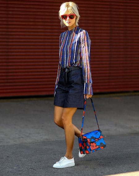 Девушка в темной джинсовой юбке, блузке в разноцветную полоску, белые кроссовки и сумка с разноцветным принтом
