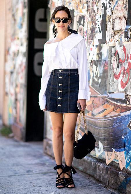 Девушка в темной джинсовой юбке на пуговицах, белая блузка, черные босоножки и сумочка
