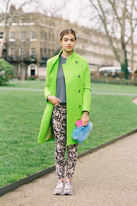Девушка в ярком салатовом пальто и брюках