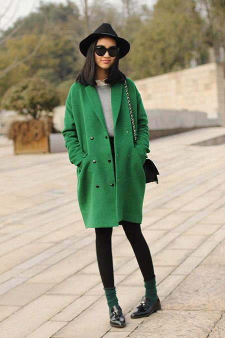 Девушка в ярком зеленом пальто и шляпе