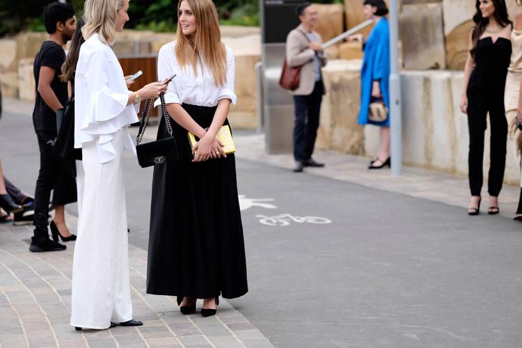 Модель в белом брючном костюме и модель в черной юбке макси и белой блузе