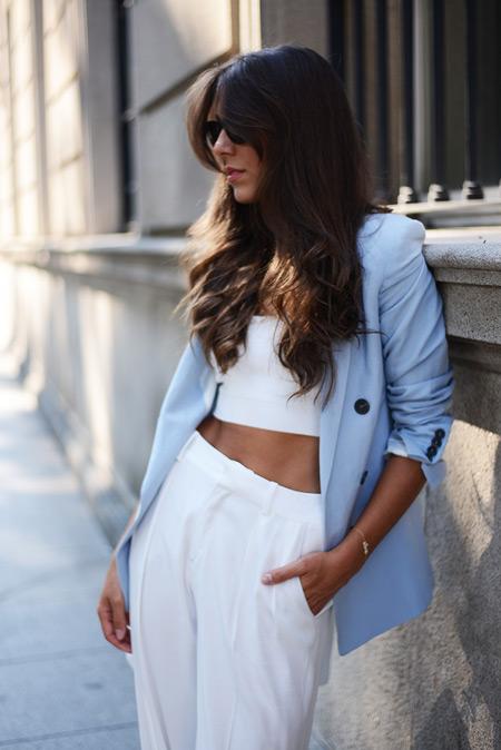 Модель в белых брюках, кроп топ и голубой жакет с черными пуговицами