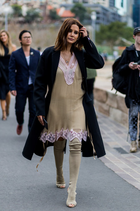 Модель в бежевом платье с кружевной отделкой, черное пальто и сапоги чулки с открытыми пальцами
