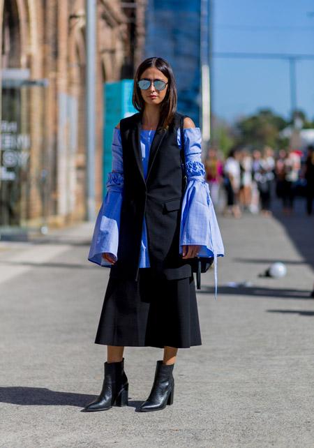 Модель в блузе с длинными рукавами клеш, черной юбке миди и жилет, черные ботильоны