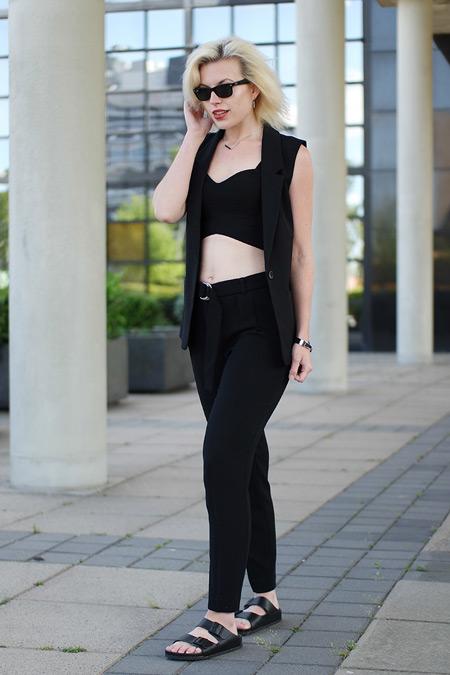 Модель в черном костюме с брюками, жилетом и кроп топ
