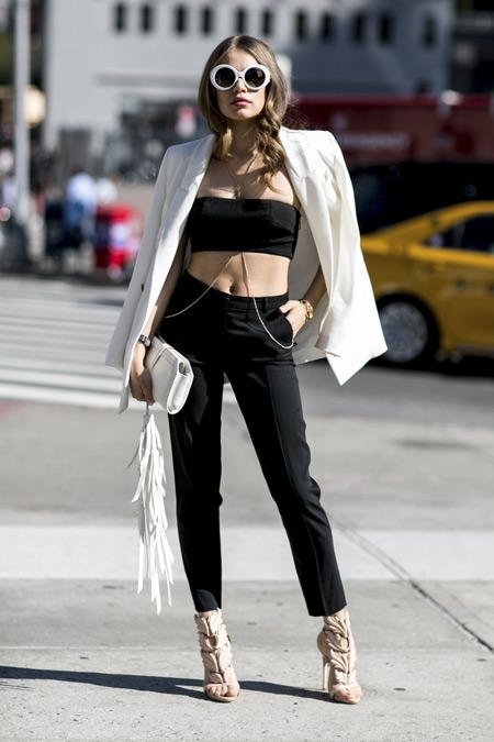 Модель в черных брюках, кроп топ и белый пиджак