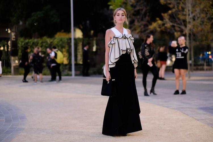 Модель в длинном платье с черной юбкой и белым объемным верхом