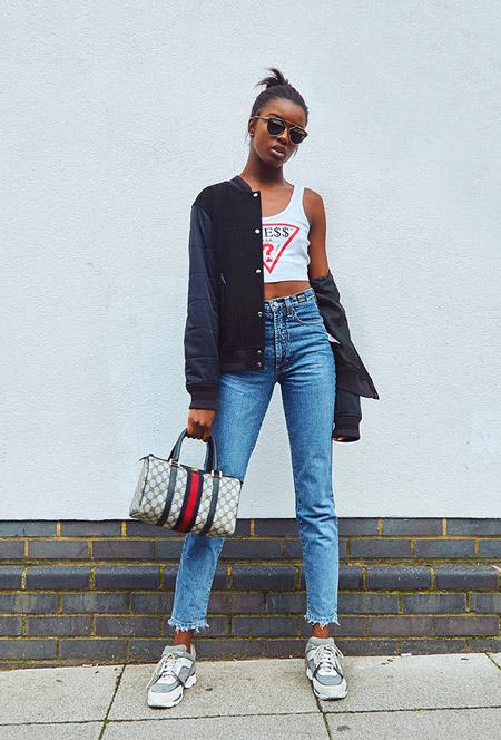 Модель в джинсах с высокой посадкой, белый кроп топ и темная куртка