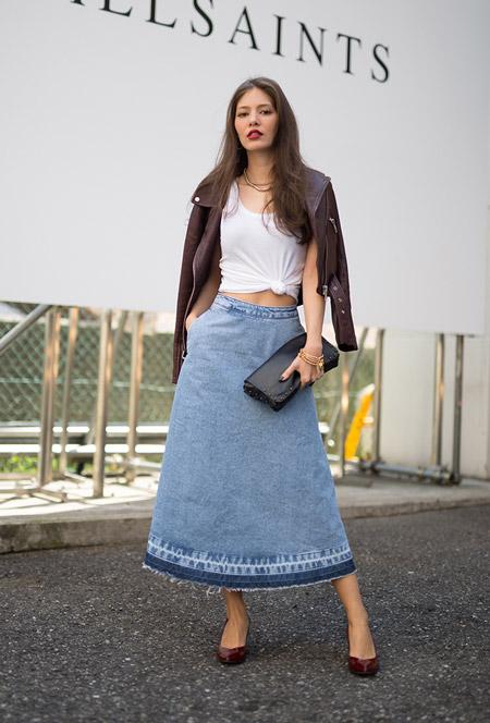 Модель в джинсовой длиной юбке, белый топ и куртка косуха