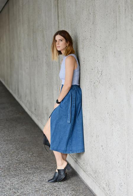 Модель в джинсовой юбке миди и голубой топ, черные сабо